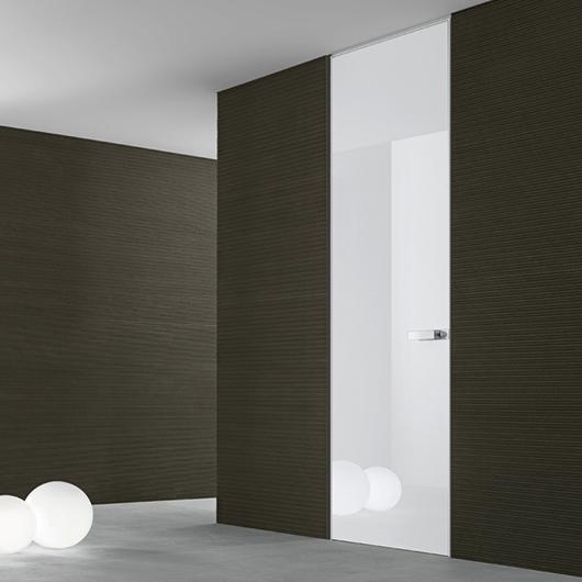 Exklusive Tür Moon von Rimadesio - Moon, eine flächenbündige lackierte Glastür, die Tür und Wand ineinander fließen lässt.