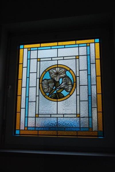 Bleiverglasung mit der Glasmalerei Lilly of England. Das handgemalte kreisförmige Blumenmotiv stellt Lilien dar.