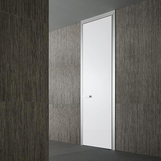 Luxor Glastür von Rimadesio. Raumhohe Tür für wahlweise Öffnung nach innen oder außen. Türpfosten glasverkleidet oder aus lackiertem Aluminium.