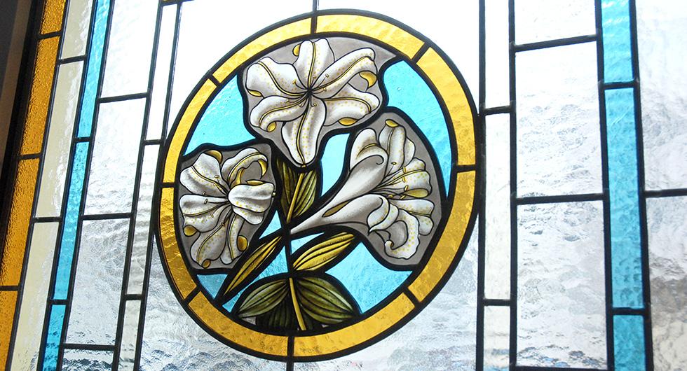 Detailansicht der Bleiverglasung mit der Glasmalerei Lilly of England. Das handgemalte kreisförmige Blumenmotiv stellt Lilien dar.