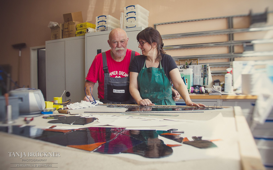 Zwei Generationen Kunstglaser in der Werkstatt von Berlin Glas beim Zuschnitt der Glasteile für die Fensterrose.