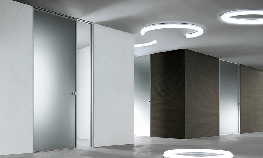 Die exklusive Design-Pendeltür und Drehflügeltür Vela von Rimadesio. Diese Innentür kann in beide Richtungen geöffnet werden.