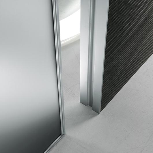 Die Drehflügeltür Vela von Rimadesio. Diese Design-Glastür kann in beide Richtungen geöffnet werden.